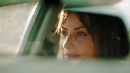 Cinematic shot of a pretty woman driving during the day.