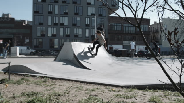 A cinematic shot of a skateboarding crashing at a Brooklyn, NYC skatepark