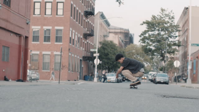 Cinematic shot of a young skateboarder in the streets of Brooklyn, NYC - slow motion