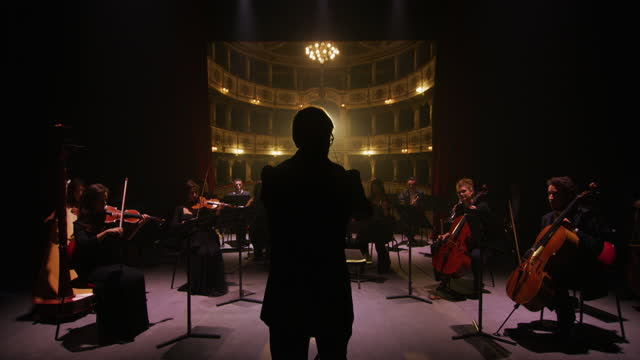 Cinematic shot of conductor directing symphony orchestra with performers playing violins, cello and trumpet