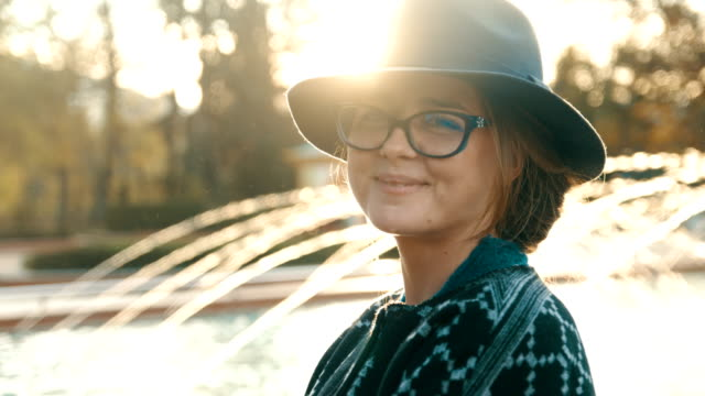 cinematic slow motion shot of a beautiful young woman standing in front of a fountain looking at camera and smiling - eyeglasses stock videos & royalty-free footage