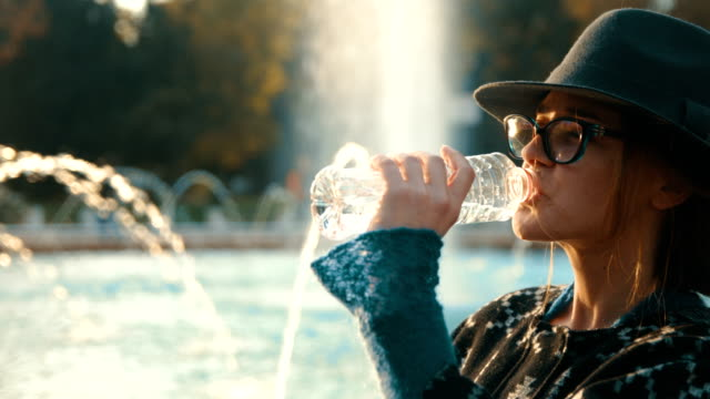 cinematic slow motion shot of a girl standing in front of a fountain and drinking water from plastic bottle - fontana struttura costruita dall'uomo video stock e b–roll