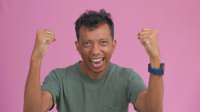 vídeos de stock e filmes b-roll de cinematic studio shot of happy asian man smiling raising his hands, making a very happy expression , winning feeling , exciting ,with pink background. - atitude