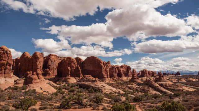 cinematic timelapse of clouds over a rocky landscape in arches national park near moab utah - moab utah stock videos & royalty-free footage