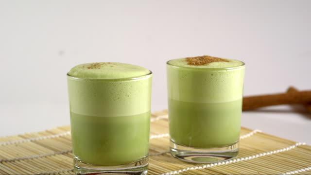cinnamon sugar falling on green matcha tea foam - drinking glass stock videos & royalty-free footage