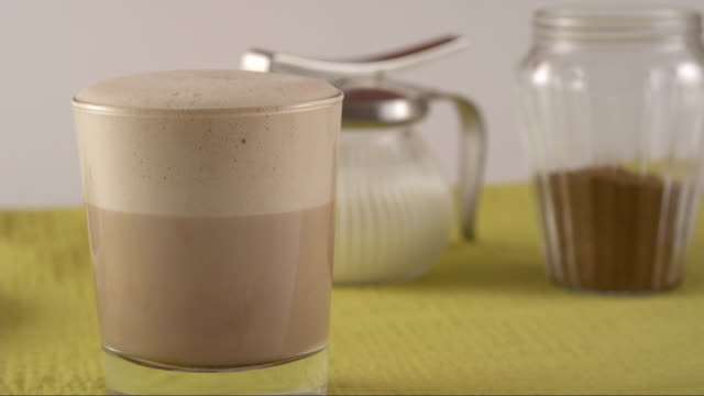 stockvideo's en b-roll-footage met cinnamon sugar falling on hot chocolate foam in highspeed - suikerpot