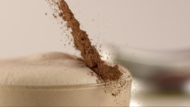 cinnamon sugar falling on hot chocolate foam in highspeed - 飲み物の泡点の映像素材/bロール