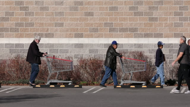 circa orem utah people pushing shopping carts walking in a line outside of store waiting their turn to shop during pandemic - orem utah stock videos & royalty-free footage