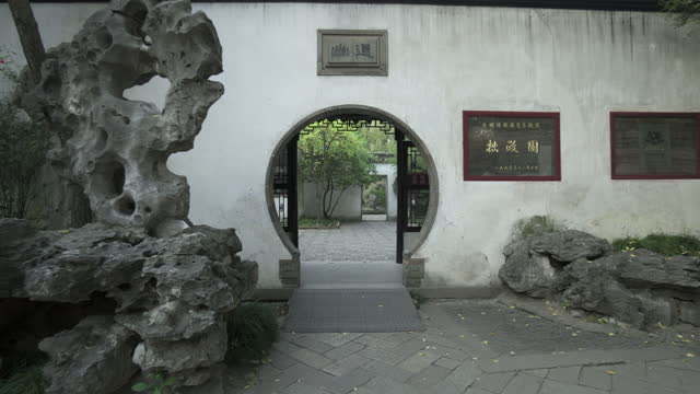 circle doorway with chinese script on wall by rocks at buddhist temple - suzhou, china - temple building stock videos & royalty-free footage