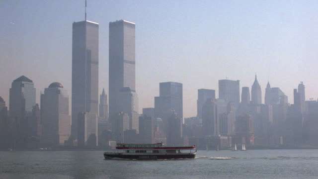 a circle line tour boat passes the manhattan skyline. - world trade center manhattan video stock e b–roll