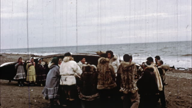 a circle of eskimos holding pieces of cloth throw a girl up in the air near the ocean while others watch. - inuit stock videos & royalty-free footage
