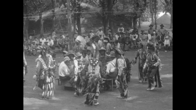 vidéos et rushes de circle of men beat a drum on the ground / a line of men in feathered regalia sits on a bench; men rise and dance around the drummers / with tents... - vêtement traditionnel