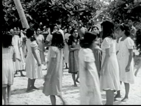 vidéos et rushes de 1949 b/w montage circle of young girls playing game juggling small coconuts with one hand. they clap for winner / likiep, marshall islands - 1949