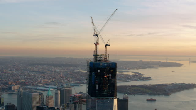 circling aerial shot of top of one world trade center at sunset - baugewerbe stock-videos und b-roll-filmmaterial