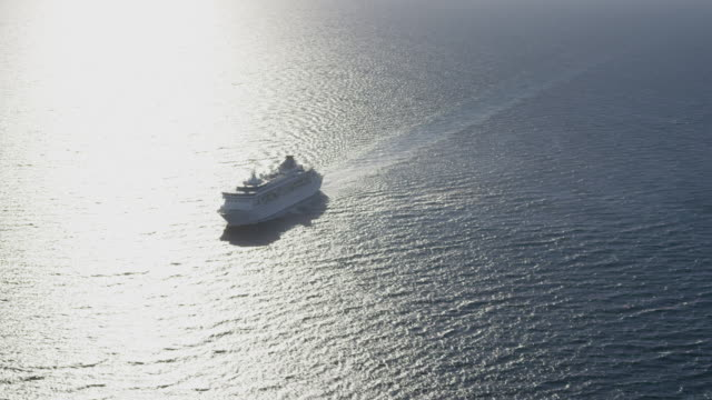 circling aerial view of cruise ship,camera moves across bow of ship right to left, red r3d 4k - kreuzfahrtschiff stock-videos und b-roll-filmmaterial