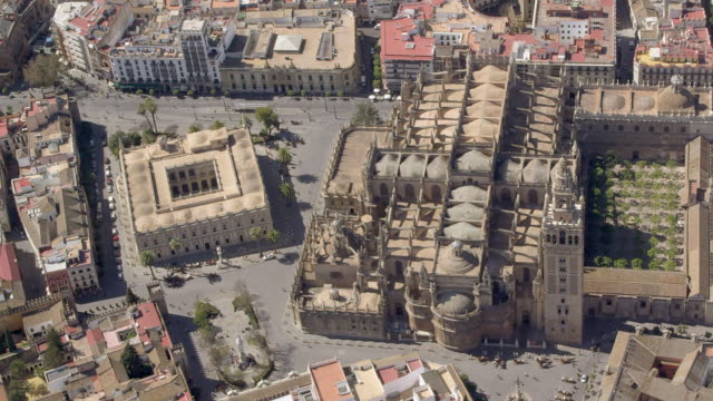 circling aerial view of seville cathedral with la giralda belfry and the archivos de las indias the general archive of the indies; the square building to the left of the cathedral) - general view stock videos & royalty-free footage