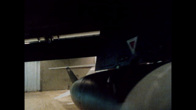 ds / circling closely around a stationary military aircraft in its hangar / united kingdom - hangar stock-videos und b-roll-filmmaterial