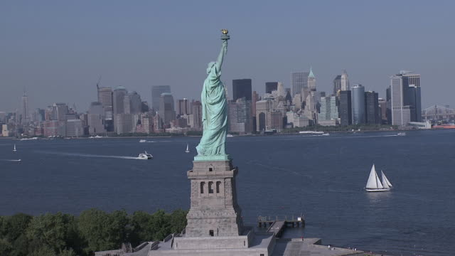 aerial circling the statue of liberty, with boats in the harbor / new york city, new york, united states - 自由の女神点の映像素材/bロール