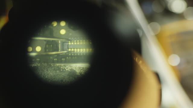 vídeos de stock, filmes e b-roll de circuit board work in microscope, close up - equipamento ótico