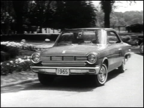 vidéos et rushes de ws circular driveway different cars drive into view on opposite sides of the driveway first is a 1965 amc ambassador 990 sedan then a 1965 rambler... - cadrage aux genoux