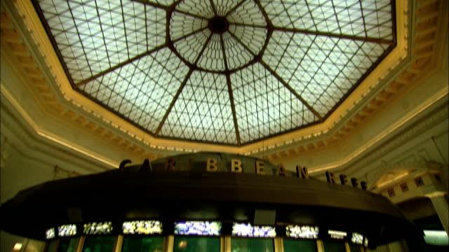 vídeos de stock e filmes b-roll de a circular fish aquarium lies below an octagonal ceiling design. - aquário john g shedd