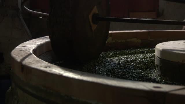 vídeos y material grabado en eventos de stock de a circular machine presses olives in greece. - pushing