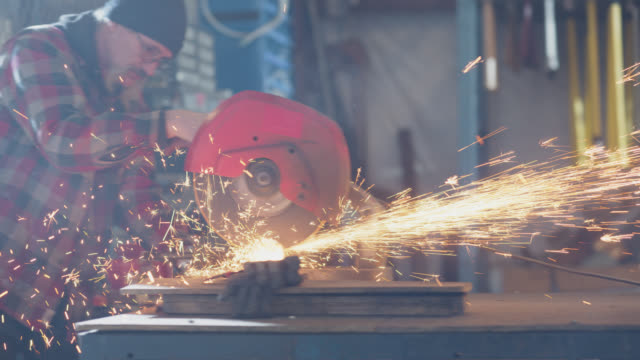 circular saw emits sparks as industry worker uses it to cut metal in warehouse - moustache stock videos & royalty-free footage