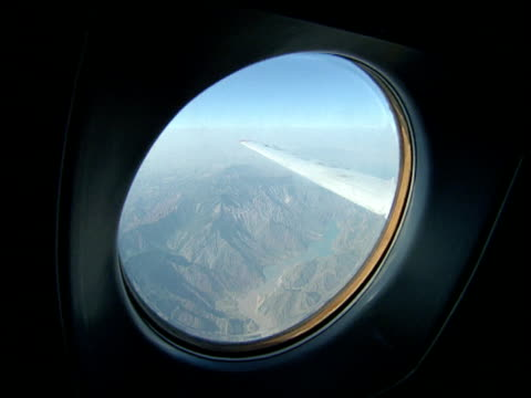 circular window of aeroplane flying above pamir mountains central asia - aircraft wing stock videos & royalty-free footage