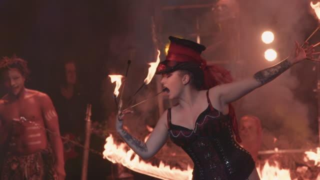 vidéos et rushes de a circus performer raises a flaming baton into the air and eats the flames during a circus performance - théâtre burlesque