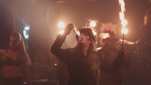 circus performer raises a flaming baton into the air and eats the flames during a circus performance - musical burlesco video stock e b–roll
