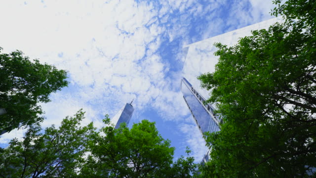 cirrocumulus clouds float above the lower manhattan skyscraper, which reflect to the building walls at new york city ny usa on may 18 2019. - cirrocumulus stock videos & royalty-free footage
