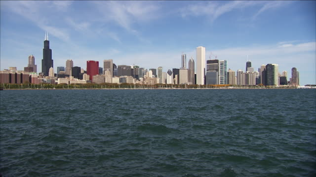 cirrus clouds hang over the chicago skyline beyond lake michigan. - two prudential plaza stock videos & royalty-free footage