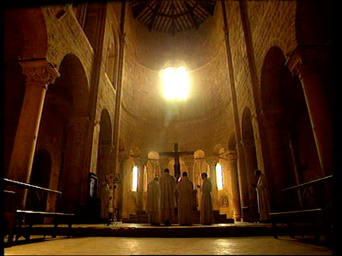 Cistercian monks at prayer standing round cross in chapel lit with gentle golden light Tuscany\n