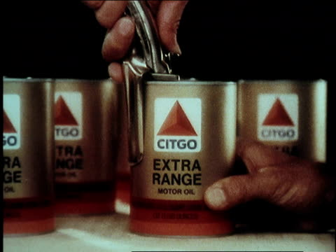 stockvideo's en b-roll-footage met 1974 montage citgo motor oil bottles sitting on automobile insurance policy written in old style calligraphy /united states - motor oil