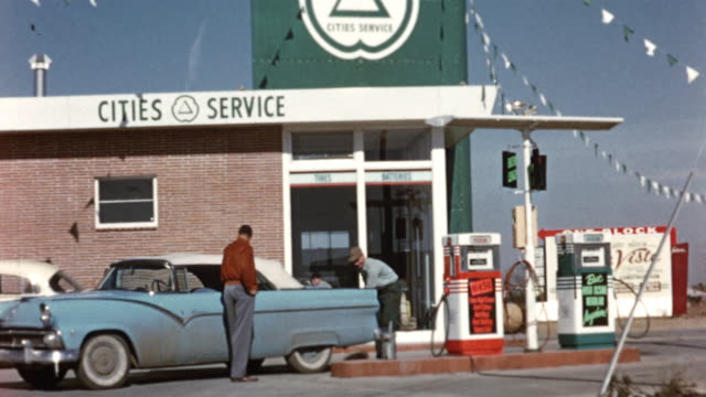 1956 WS TD Cities Service gas station, car getting serviced / USA