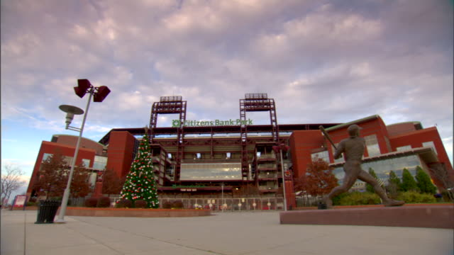 citizens bank park third base gate christmas tree on left mike schmidt statue on right blue sky w/ white cumulus clouds bg pan/reverse multiple takes... - philadelphia phillies stock-videos und b-roll-filmmaterial
