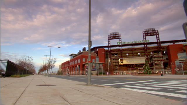 citizens bank park third base gate sidewalk street partial metal gate fg blue sky w/ white cumulus clouds bg pan/reverse multiple takes sports... - philadelphia phillies stock-videos und b-roll-filmmaterial