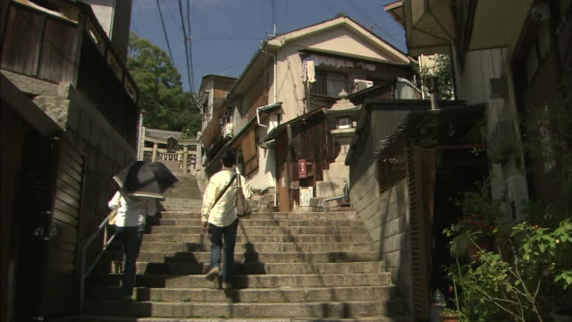 citizens climb stone steps between houses in onomichi. - onomichi hiroshima stock videos and b-roll footage