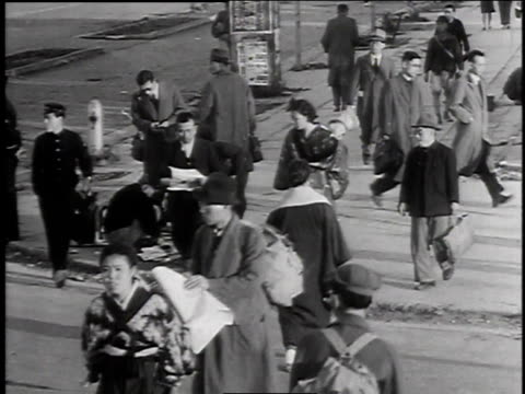 citizens crossing street / kneeling girl selling newspapers on street / people purchasing newspapers - 1940~1949年点の映像素材/bロール