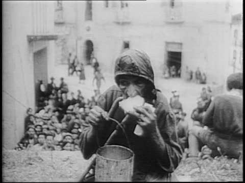 Citizens of Cassino Italy gather in streets for food / Italian refugees collect water man stirs soup in large barrels / officer pouring soup into...
