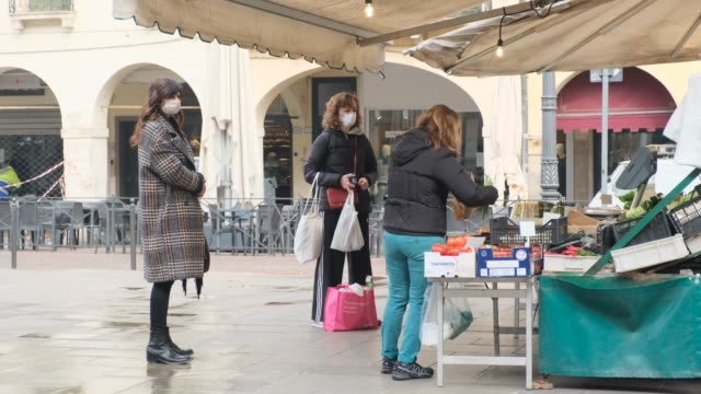 citizens of padua cross the streets of the city almost deserted wearing an ffp2 mask to protect themselves from the infestation of covid19 which led... - infestation stock-videos und b-roll-filmmaterial