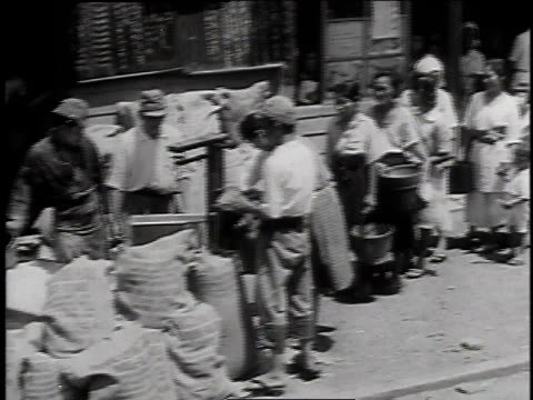 citizens queuing for food rations / workers distributing food from sacks - 1947年点の映像素材/bロール