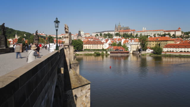 citizens use the charles bridge to cross the river vltava as ferryboats sail beneath. - charles bridge stock videos and b-roll footage
