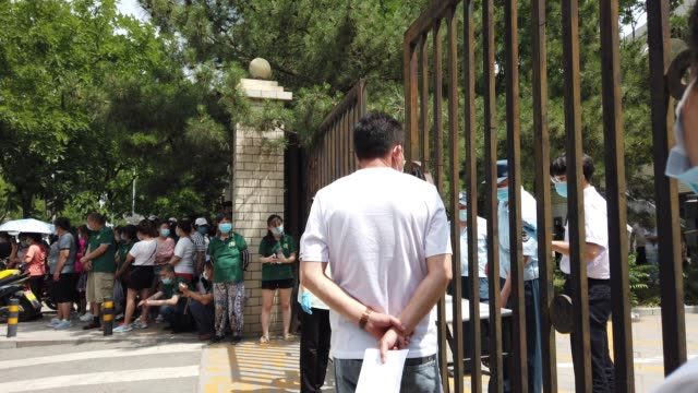 citizens who visited or live near xinfadi market queue for a nucleic acid test during the coronavirus pandemic at a sports center on june 16, 2020 in... - 酸点の映像素材/bロール