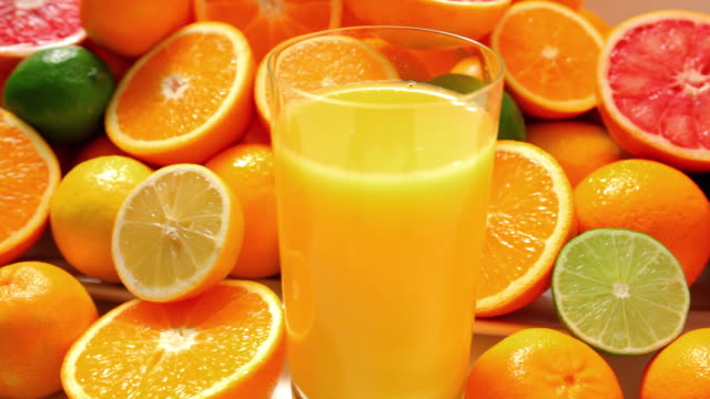 cu citrus fruits and glass of fresh juice / london, united kingdom - inquadratura dall'alto di un tavolo video stock e b–roll