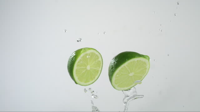 citrus lime flying and creating splashing droplets - ライム点の映像素材/bロール