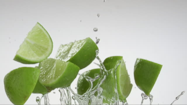 citrus lime flying and creating splashing droplets - lime stock videos & royalty-free footage