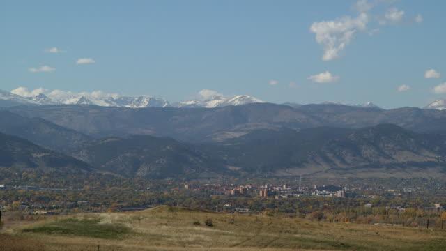 vídeos de stock, filmes e b-roll de xws city at base of rocky mountains blue sky w/ white clouds grassy hill fg snowcapped peaks bg - boulder city