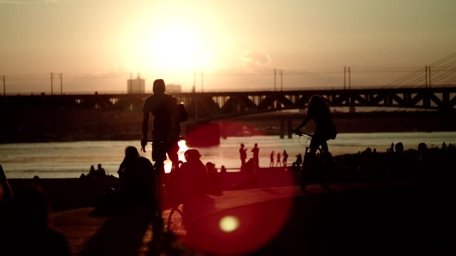 city beach party. industrial area. sunset silhouettes - riverbank stock videos & royalty-free footage