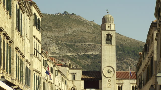 City bell tower w/ clock on Luza Square buildings either side of Stradun hillside BG Europe Mediterranean main street landmark historic